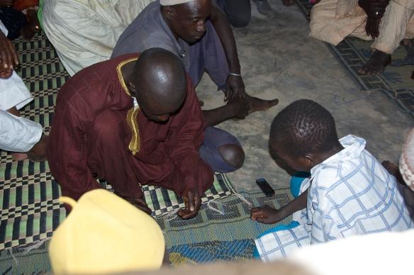 A young talibé reciting verses from the Koran to his Koranic teacher and Imam Ousmane Samb