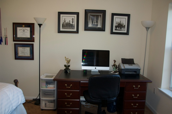 My desk and framed artwork, bachelor's degree,  a certificate from my boss at BYU, and my graduation tassels
